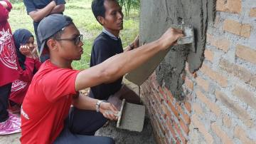 Youth learning to construct a toilet.